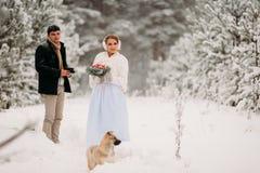 Pares con un perro en bosque del invierno Imágenes de archivo libres de regalías