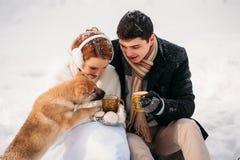 Pares con un perro en bosque del invierno Fotos de archivo libres de regalías
