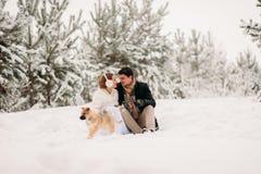 Pares con un perro en bosque del invierno Foto de archivo