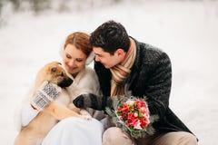 Pares con un perro en bosque del invierno Imagenes de archivo