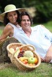 Pares con una cesta de fruta Imagen de archivo