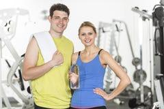 Pares confiados con la toalla y la botella de agua en gimnasio Foto de archivo libre de regalías
