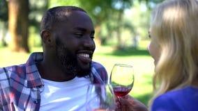 Pares contentos que gozan de la bebida en la comida campestre, fecha romántica, tradiciones del vino imagen de archivo