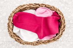 Pares cor-de-rosa, brancos e roxos de peúgas da criança em Straw Basket Imagens de Stock Royalty Free