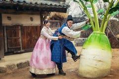 Pares coreanos jovenes en el hanbok wolking en el parque foto de archivo