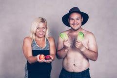 Pares corpulentos engraçados com frutas e legumes Foto de Stock