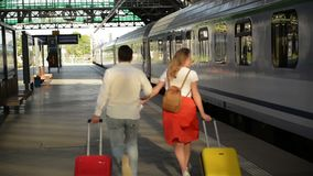 Pares corrientes con una maleta en una estaci?n de tren Mujer que sostiene pasaportes en sus manos mientras que se sale el tren metrajes