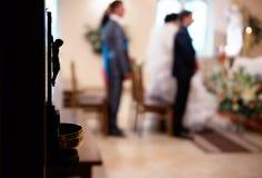 Pares cristianos de la boda en la iglesia católica Foco en el statu de Jesús Fotografía de archivo