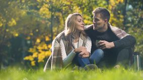 Pares cubiertos con la tela escocesa que se sienta en parque del otoño, té caliente de consumición y el discurso almacen de video