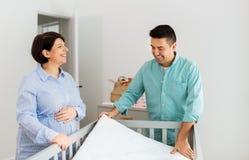 Pares da família que arranjam a cama de bebê com colchão imagem de stock
