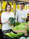 Pares da família que compram legumes frescos no mercado Fotografia de Stock Royalty Free