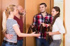 Pares da família que dão boas-vindas a visitantes em casa Imagem de Stock