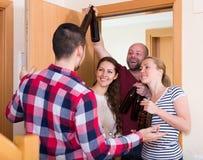 Pares da família que dão boas-vindas a visitantes em casa Imagens de Stock