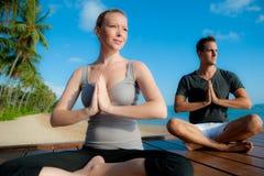 Pares da ioga por Oceano Foto de Stock