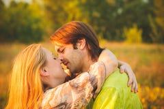 Pares da lua de mel românticos no amor no por do sol do campo e das árvores Pares novos felizes do recém-casado que abraçam aprec Imagem de Stock