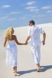 Pares da mulher do homem que guardam as mãos que correm a praia Fotos de Stock