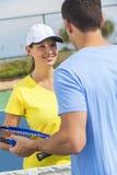 Pares da mulher do homem que jogam o tênis ou a lição Imagens de Stock Royalty Free