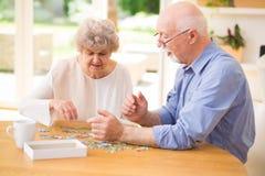 Pares da pessoa idosa que montam o enigma junto foto de stock