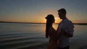 Pares da silhueta que beijam sobre o fundo do por do sol filme