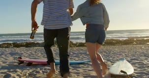 Pares da vista traseira que guardam as mãos com a garrafa de cerveja que corre para a praia 4k filme