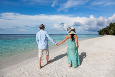 Pares das férias que andam na praia tropical Maldivas Fotos de Stock