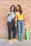Pares das jovens mulheres que fazem um selfie Atr?s da parede de tijolo Conceito positivo da emoção e da tolerância imagens de stock