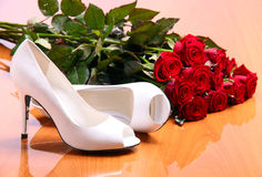Pares das sapatas fêmeas brancas e grupo de rosas vermelhas Fotografia de Stock