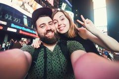Pares datando felizes no amor que toma a foto do selfie no Times Square em New York quando curso nos EUA na lua de mel Imagens de Stock