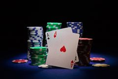 Pares de áss e de microplaquetas de pôquer no fundo preto Imagens de Stock