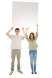Pares de adolescentes con el panel blanco Fotografía de archivo libre de regalías
