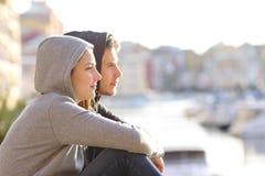 Pares de adolescentes que contemplam o horizonte em uma cidade da costa foto de stock