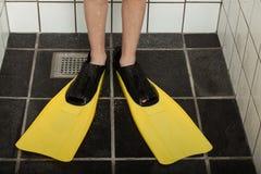 Pares de aletas do mergulho nos pés na tenda de chuveiro Imagens de Stock
