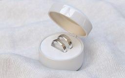 Pares de alianças de casamento do ouro na caixa branca da joia Foto de Stock