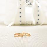 Pares de alianças de casamento na frente do coxim luxuoso Imagens de Stock