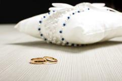 Pares de alianças de casamento na frente do coxim luxuoso no assoalho Imagens de Stock