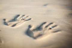 Pares de amantes em um por do sol bonito sobre o oceano Pares em umas férias românticas Imprima pares de mãos na areia, casamento Fotos de Stock Royalty Free