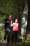 Pares de amantes jovenes que se ejecutan en el parque Foto de archivo libre de regalías