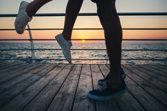 Pares de amantes novos do moderno que beijam, próximos acima nos pés e nas sapatilhas na praia no céu do nascer do sol em horas d Foto de Stock Royalty Free