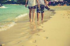 Pares de amantes que andam no cada um no nascer do sol - o pé imprime a praia Foto de Stock Royalty Free