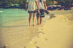 Pares de amantes que andam no cada um no nascer do sol - o pé imprime a praia Imagens de Stock