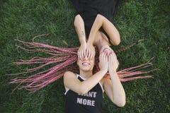 Pares de amigos adolescentes que jogam na grama Fotografia de Stock