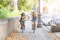 Pares de amigos con las bicicletas en carril de la bici Imagenes de archivo
