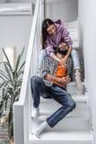 Pares de amor à moda que sentam-se em escadas ao descansar em casa fotografia de stock royalty free