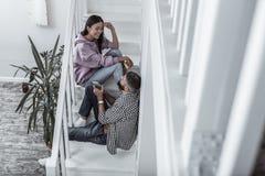 Pares de amor bonitos que têm a conversação em casa que senta-se em escadas fotos de stock