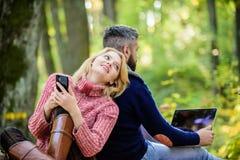 Pares de amor felizes que relaxam no parque com dispositivos m?veis Os povos modernos envolveram sempre uma comunica??o em linha  imagem de stock