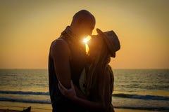 Pares de amor ? moda que abra?am-se na praia no por do sol Homem e mulher na viagem da lua de mel do feriado foto de stock royalty free
