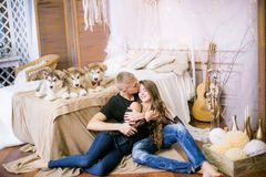 Pares de amor novos alegres que sentam-se no quarto ao expressar o amor com cachorrinhos fotografia de stock royalty free