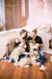 Pares de amor novos alegres que sentam-se no quarto ao expressar o amor com cachorrinhos imagem de stock