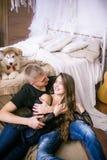 Pares de amor novos alegres que sentam-se no quarto ao expressar o amor com cachorrinhos fotos de stock royalty free
