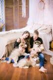 Pares de amor novos alegres que sentam-se no quarto ao expressar o amor com cachorrinhos fotos de stock